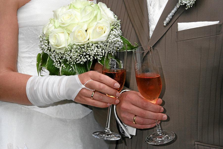 Brautpaar mit Brautstrauss und Sekt
